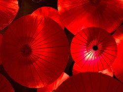 background of beautiful Asian traditional decoration with red umbrellas hanging on the ceiling, interior design element of celebration Japanese Chinese Vietnam style, display of Asian culture symbol