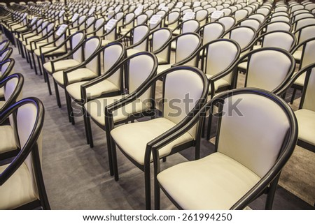 background of beige armchairs in conference hall in perspective Rows of new elegance chairs stand on brown wooden texture floor Empty seat