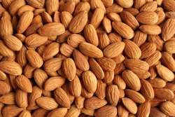 Background of big raw peeled almonds situated arbitrarily