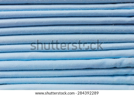 Background of blue fabric folded in a pile close-up.