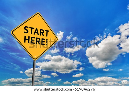 Background of blue sky with cumulus clouds and yellow road sign with text Start Here #619046276