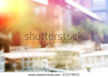 Background of blurred cafe on street of city. Tables and chairs outside in natural bokeh