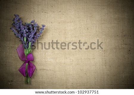 Background of burlap with a bouquet of of lavender