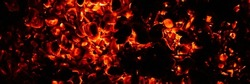 background of burning and glowing hot coals. smoldering embers of fire. flicker of burning coals at night. banner