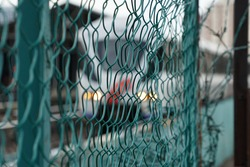 Background of chain link fence and blurred light rail train backdrop