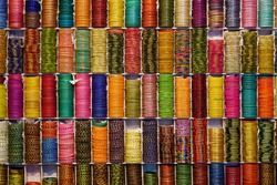 Background of colorful bangles stacked in a shop in India with glitter and plain colored bangles. The bangles are made of glass, metal or lac and worn regularly or on special occasions by Indian women