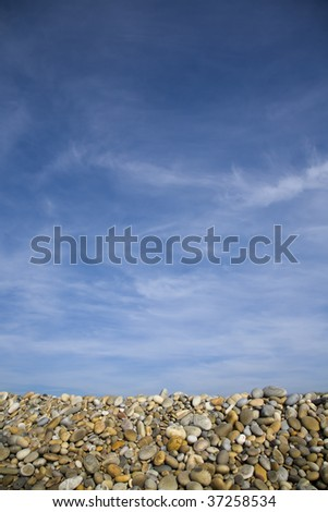Background of colorful beach pebbles and blue sky