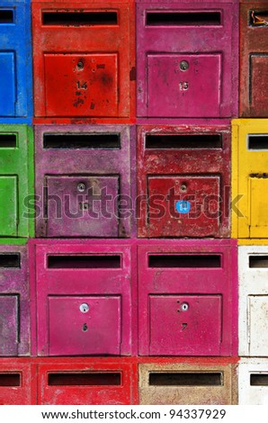 background of colorful old and rusty mailboxes