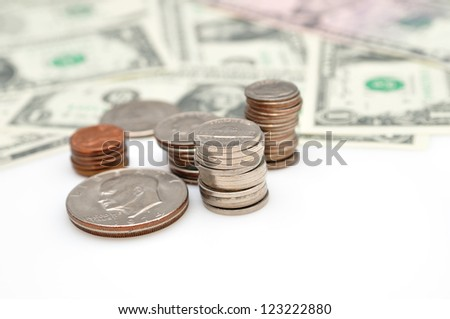 Background of dollar banknotes and coins, with selective focus, isolated on white background.