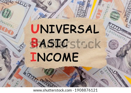Background of dollar bills with Universal basic income (UBI) text written with marker on old torn paper. Selective focus Foto stock ©