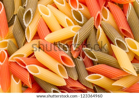 Background of dry raw in three different colors penne pasta