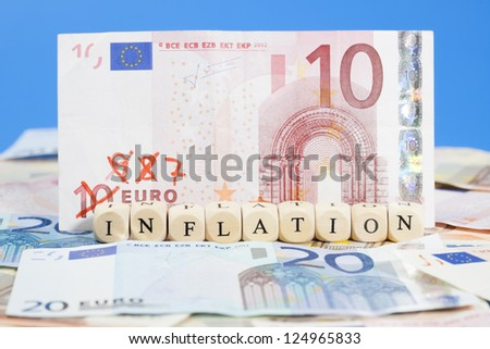 "Background of Euro banknotes on the ground, one 10 Euro note with 9, 8, 7... written on it. Letter dices forming the word ""Inflation"". Short Depth of field with front and back part blurred."