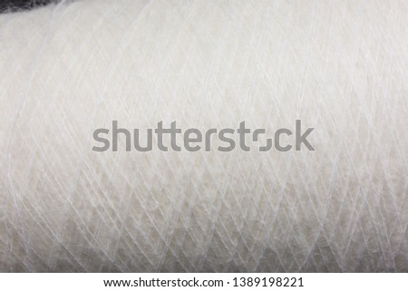 background of fluffy white mohair wool on a cone