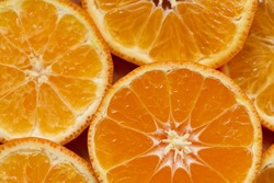Background of fresh and juicy tangerine slices or mandarin fruit, macro, shallow depth of field