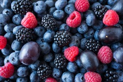 Background of fresh fruits and berries. Ripe blackberries, blueberries, plums, raspberries. Mix berries and fruits. Top view. Background berries and fruits. Black-blue and red food.