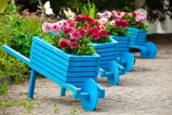 Background of garden design. Landscaping in park with blue handmade carts decorated with flowers