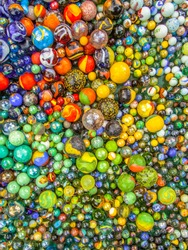 Background of glass marbles of different sizes in a color pattern