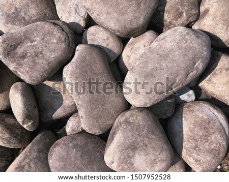 Background of gray smooth large pebbles. Large pebbles closeup. Gray background of stones.