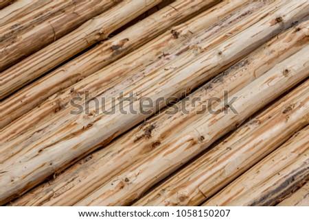 Background of hand peeled pine tree diagonal logs #1058150207