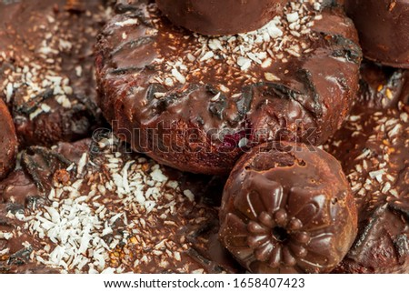 Background of homemade chocolate sweets. Natural chocolate candies. Coconut raisin cookies. Top view. Selective focus. Healthy and delicious meal. Harmless treat to tea for vegan and vegetarian diet