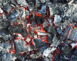 Background of hot charcoal, backdrop of ember after fire burnt out. Smoldering charcoal with dying fire, remains of burning firewood, wood ash. Closeup for product photo, coal industry, BBQ, insurance
