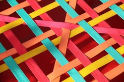 Background of intertwined multicolored textile ribbons