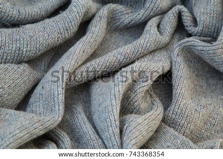background of knitted gray linen of goat's wool made with knitting needles or on a knitting machine laid in big waves. #743368354