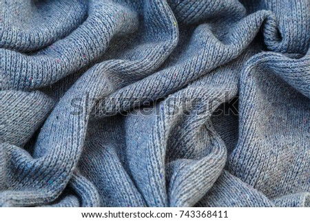 background of knitted gray linen of goat's wool made with knitting needles or on a knitting machine laid in big waves. #743368411