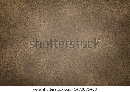 Background of light bronze suede fabric closeup. Velvet matt texture of brown nubuck textile with vignette. #1490895488