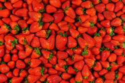Background of many pieces of strawberries, overhead view, studio food photography. Macro