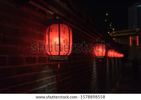 Background of many red lanterns hanging inside Chinese city walls. Text translation on lantern: Blessing, Ancient Chinese characters of various blessings, auspicious, Safety