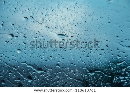 Background of moving rain drops on a window glass in a rainy day