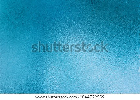 Background of natural water condensation, window glass with high air humidity, large drops drip. Collecting and streaming down