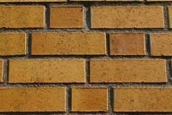 Background of old vintage yellow brick wall. Gray sealant. Aged paint at background exterior area, grungy rusty blocks of stonework technology color horizontal architecture wallpaper. Stockholm Sweden