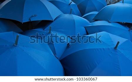 background of open blue umbrellas receding into distance #103360067