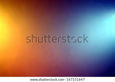 Background of orange and blue color lights shining through fog