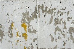 Background of painted white concrete wall with peeling paint and flecks of dark grey and gold