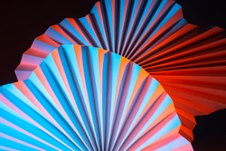 Background of paper fans of complex shape. Bright abstract background with dark base. Cardboard fans with a three-dimensional effect. Sometimes blurry image of three-dimensional geometric shapes.