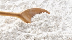 Background of potato starch flour powder texture close-up.Wooden spoon scoops potato starch.