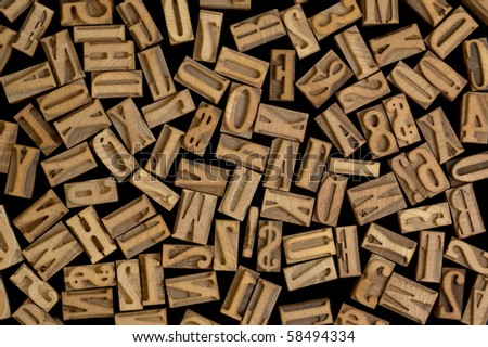 background of randomly placed wooden letterpress printing blocks, black background