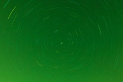Background of round or circular star track or trajectory on the green clear night sky. Symbol of space, cosmos, expanse infinity and universe