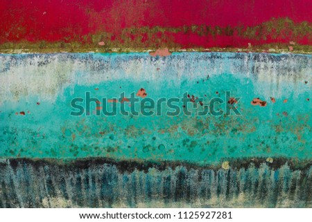 Background of rusty, red, blue, turquoise, black and yellow colored metal surface.