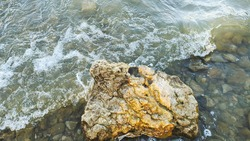 Background of sea stones and the sea serf for design.Sea surf, the wave hits the rocks. Coastline foam from breaking on the rocks of the sea surf. Wet stones and waves.