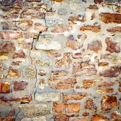 Background of stone wall texture. closeup of ancient cracked stone wall