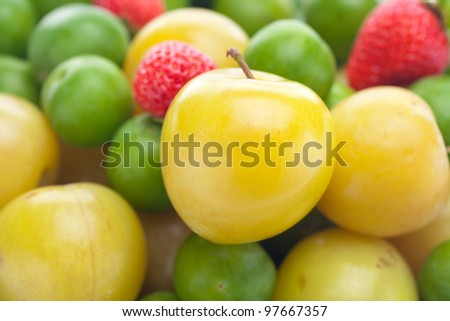background of  strawberry, green and yellow plum