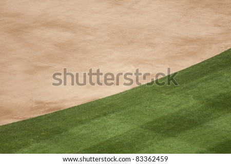 Background of the edge of the infield dirt and grass at a baseball stadium.