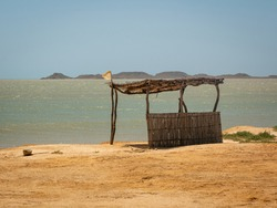 Background of the Sea at Bahia Honda Beach with a Ecological Little Store Made from Dried Banana Leaves and Logs in La Guajira, Colombia
