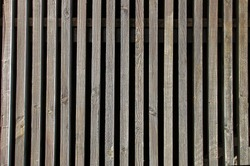 background of vertical old wooden battens with dark spaces