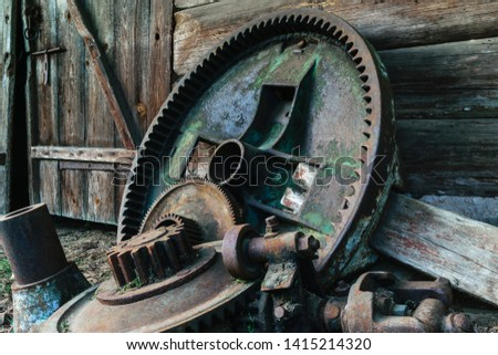 Background of very old and rusty huge rural metal device mechanical parts lying near the barn #1415214320