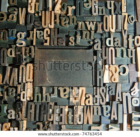 Background of vintage wooden print letter cases around a capital L